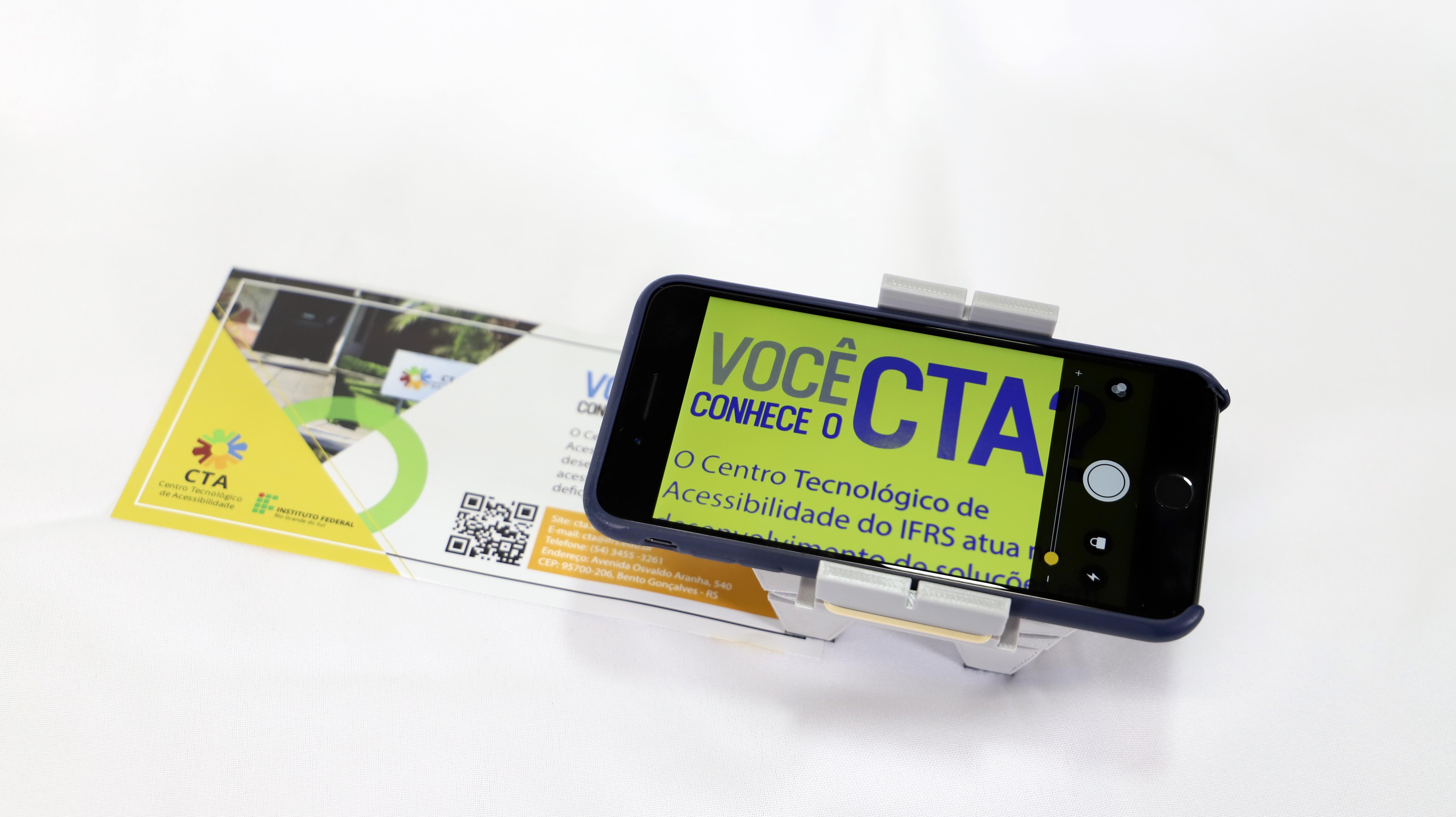 smartphone acoplado ao suporte, com lupa ativada no contraste de cores azul e amarelo