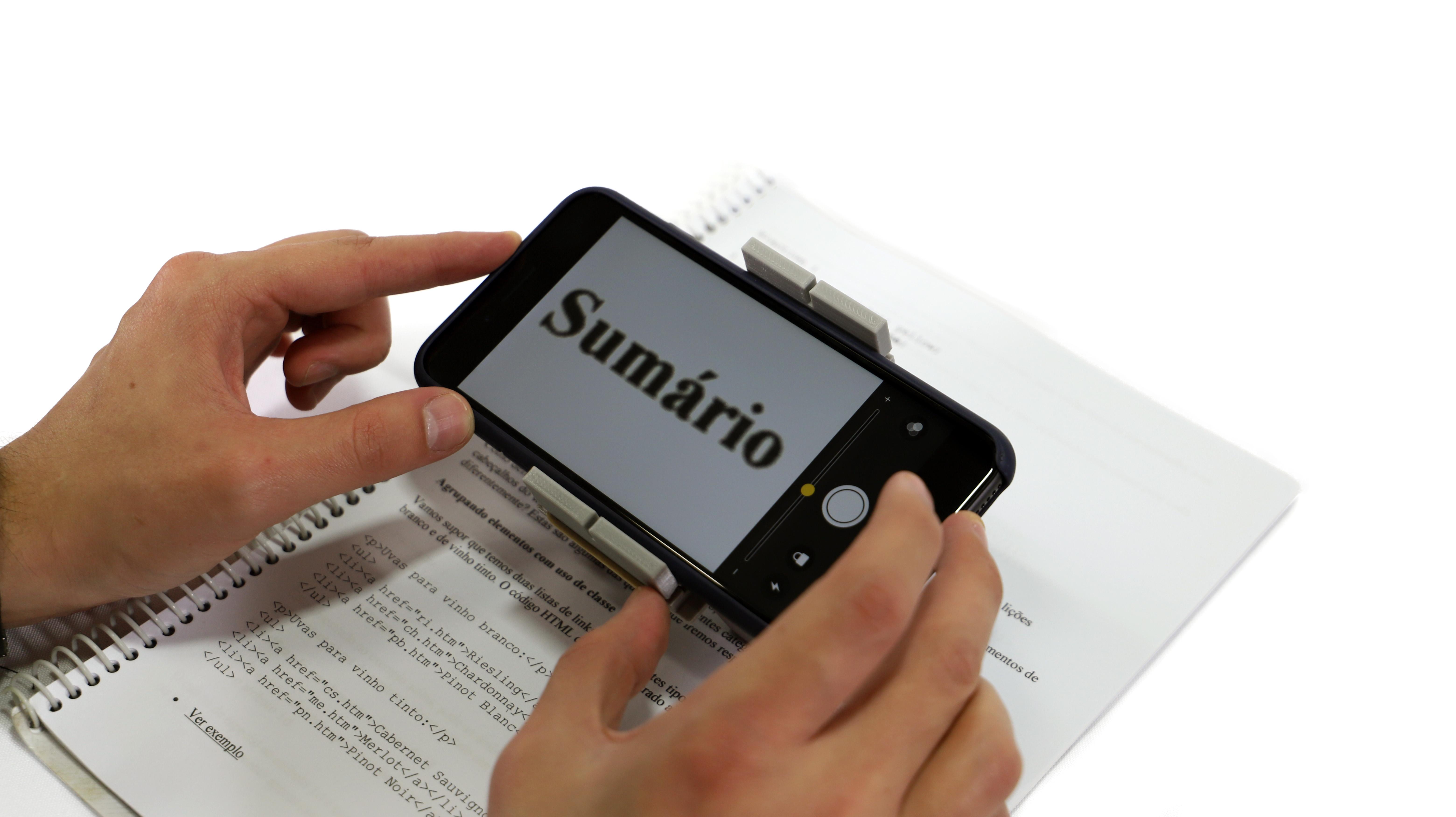 smartphone acoplado ao suporte, com lupa ativada no contraste de cores preto e branco