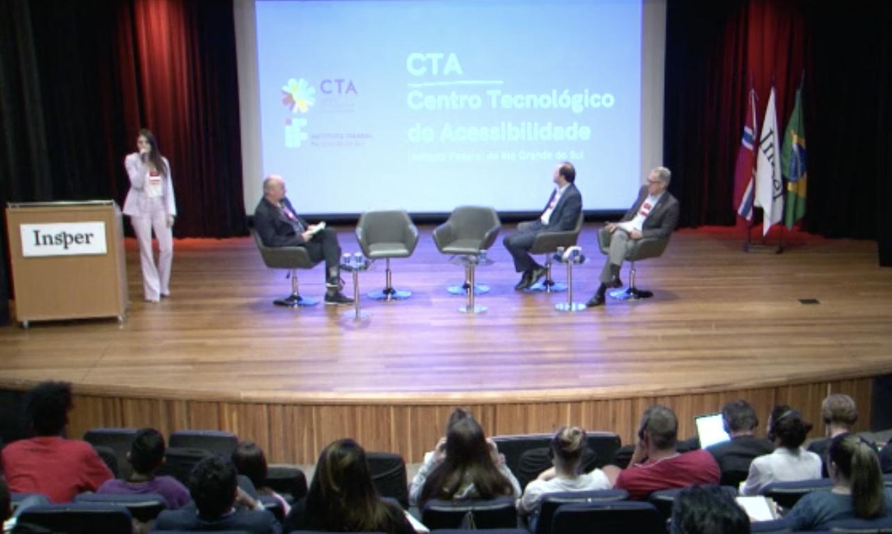 Bruna Salton em pé no palco falando ao microfone. No telão, apresentação intitulada Centro Tecnológico de Acessibilidade do IFRS.