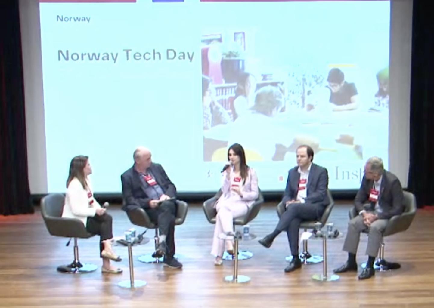Cinco pessoas no palco, duas mulheres e três homens, sentados em cadeiras