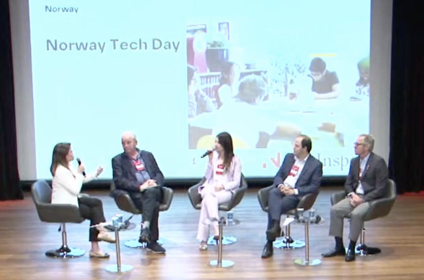 Cinco pessoas sentadas em cadeiras no palco, duas mulheres e três homens. Atrás deles, um telão com o título do evento.