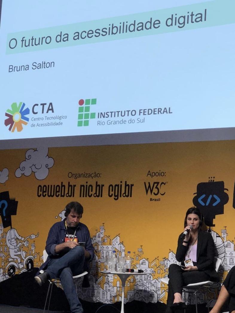 Bruna Salton, sentada, ao lado de Reinaldo Ferraz. Atrás deles, um telão com a apresentação intitulada O futuro da acessibilidade digital.