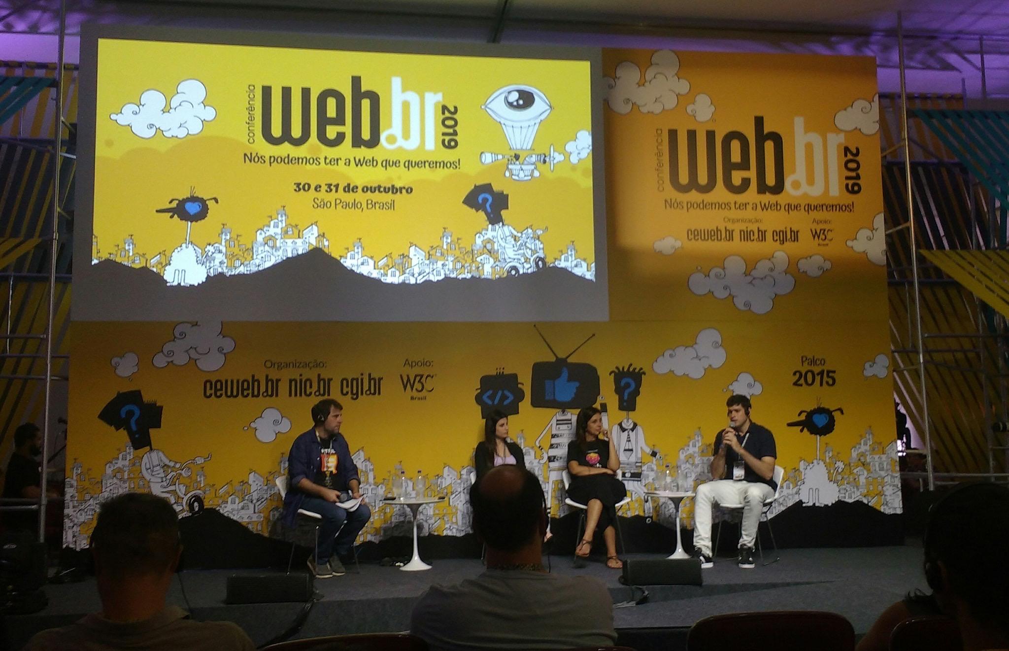 Palco do evento webbr com os palestrantes sentados em frente ao telão
